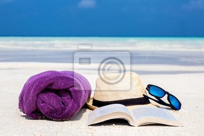 Fototapeta Ręcznik, kapelusz, książka i okulary na plaży