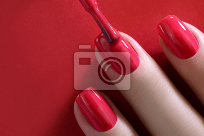 Fototapeta Red Finger nail point isolated red background with nail polish. Painting nails.