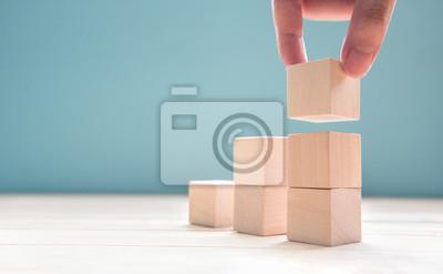 Fototapeta Ręka układa drewnianego sześcianu sztaplowanie jako kroka schodek. Proces sukcesu wzrostu koncepcji biznesu na niebieskim tle, kopia przestrzeń.