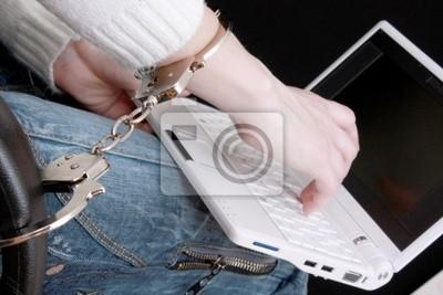 Ręka w kajdankach na laptopie