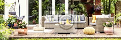 Fototapeta Relaksujące miejsce na ciepły, letni dzień - stylowy drewniany taras z wiklinowymi meblami ogrodowymi, poduszkami, roślinami i kwiatami