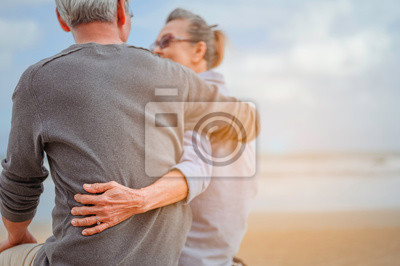 Fototapeta Retirement couple sitting by the sea, women embrace husbands and look at each other at the beach in the morning, life insurance plan at the retirement concept.