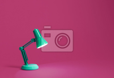 Fototapeta Retro green desk lamp turned on and bent over shining on a bright pink background.  Landscape orientation with a left side composition leaving room for text and copy space.