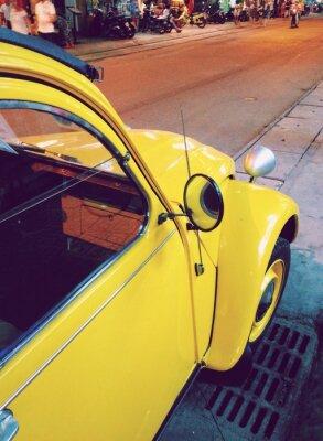 Fototapeta retro żółty samochód na ulicy