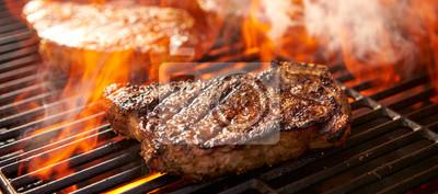 Fototapeta rib-eye steaks cooking on flaming grill panorama