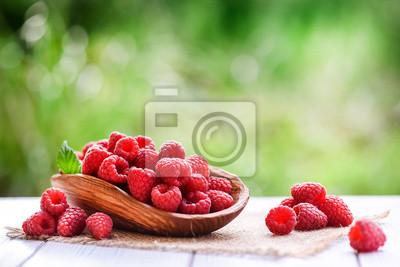 Fototapeta Ripe fresh raspberry in wooden rustic bowl on table.