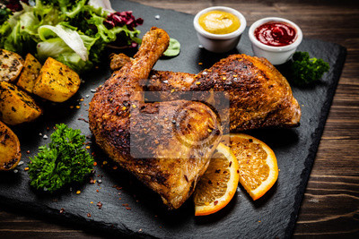 Fototapeta Roast chicken legs on black stone plate