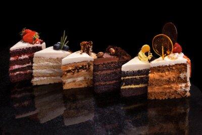 Fototapeta Różne duże kawałki różnych ciast: czekolada, maliny, truskawki, orzechy, jagody. Kawałki ciasta na czarnym stole.