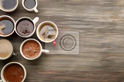Różne filiżanki kawy na drewnianym stole, odgórny widok