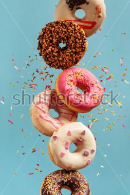 Fototapeta Różnorodni dekorujący donuts w ruchu spada na błękitnym tle. Słodkie i kolorowe pączki spadające lub latające w ruchu.