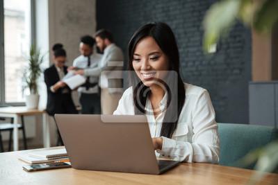 Fototapeta Rozochocona młoda azjatykcia biznesowa kobieta używa laptop