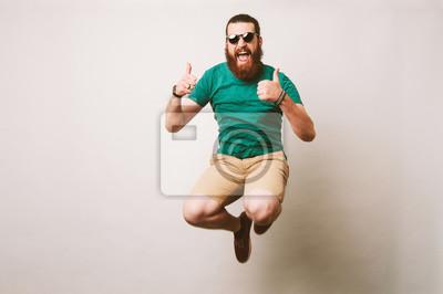 Fototapeta Rozochocony brodaty modnisia mężczyzna z okularami przeciwsłonecznymi skacze nad białym tłem i pokazuje aprobaty