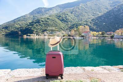 Fototapeta Różowa walizka z słomkowym kapeluszem na plaży. Pojęcie podróży, wakacji, turystyki kobiecej, podróży, przygody. Natury tło niesamowity widok z błękitnym jeziorem, góry, jesień krajobraz.
