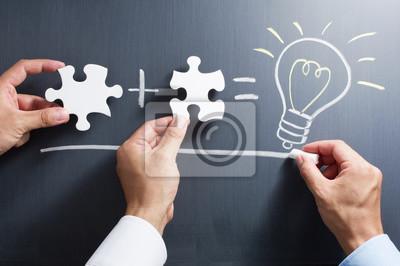 Fototapeta Rozwiązując zagadkę razem. Rysunek żarówki na tablicy. Łącząc wiedzę do opracowania nowego pomysłu.
