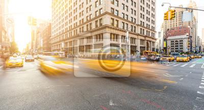 Fototapeta Ruchliwym skrzyżowaniu drogowym na Manhattanie w Nowym Jorku o zachodzie słońca
