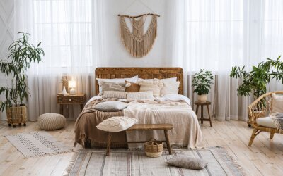 Fototapeta Rustic home design with ethnic boho decoration. Bed with pillows, wooden furniture