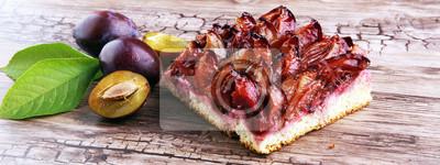 Rustykalny śliwkowy tort na drewnianym tle z śliwkami w pobliżu