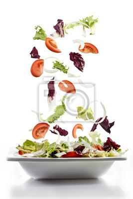 Fototapeta Sałatka ze świeżych warzyw spadają na talerzu
