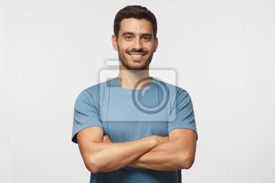 Fototapeta Salowy portret młody europejski caucasian mężczyzna odizolowywający na szarym tle, stojący w błękitnej koszulce z krzyżować rękami, uśmiechnięty i patrzejący prosto przy kamerą