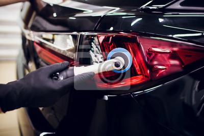 Fototapeta Samochodowe połysku wosku pracownika ręki trzyma polerowania i połysku szczegóły lub valeting samochodowego taillight czerwonego samochód