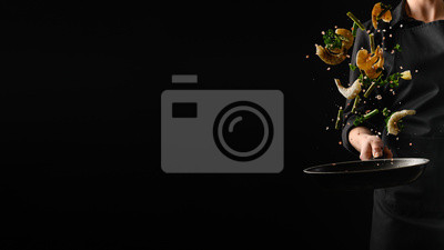 Fototapeta Seafood, frying shrimp with vegetables, a chef on a black background. Advertising banner for the sale of seafood, on a black background for design