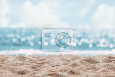 Fototapeta Seascape abstract beach background. blur bokeh light of calm sea and sky. Focus on sand foreground.