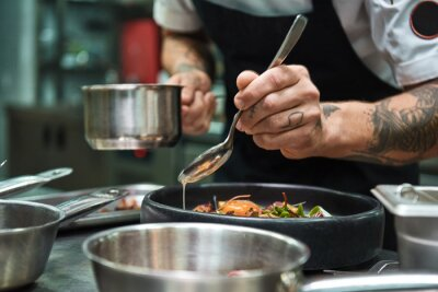 Fototapeta Secret recipe. Close up photo of chef hands with several tattoos adding a sauce to italian pasta Carbonara.