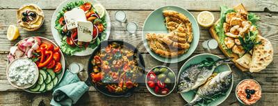 Fototapeta Selection of traditional greek food - salad, meze, pie, fish, tzatziki, dolma on wood background, top view