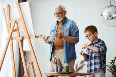 Fototapeta Senior artist and his small grandson use artist's pallete and paint on canvas together.