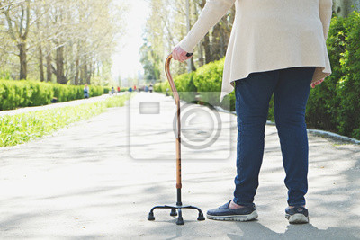 Fototapeta Senior disabled caucasian woman hands on cane outside nursing home park. Close up of elderly lady holding a walking stick outdoors of healthcare facility on the sunny day.