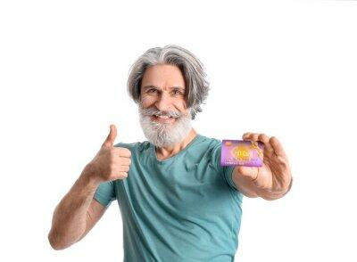 Fototapeta Senior man with gift card showing thumb-up on white background