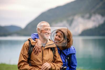 Fototapeta Senior pensioner couple hiking by lake in nature, resting.