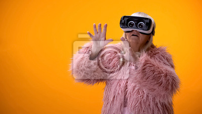 Fototapeta Senior woman in funny coat and VR headset playing video game, hi-end innovations