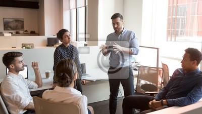 Fototapeta Serious team leader talk to diverse business people at meeting