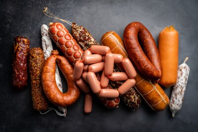 Fototapeta Set of different types of sausages, salami and smoked meat with basil and spices on a black background. Top view.