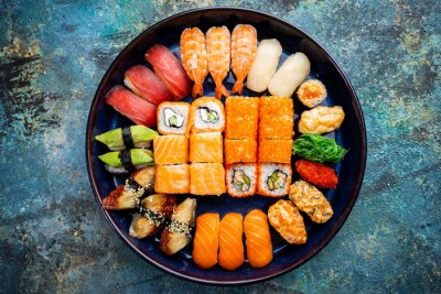 Fototapeta Set of sushi and maki with soy sauce over blue stone background. Top view with copy space