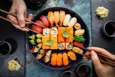 Fototapeta Set of sushi and maki with soy sauce with human hands over blue background. Top view with copy space