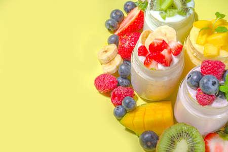 Fototapeta Set of various fruit and berry yogurts in glass jars. Variety healthy Breakfast yoghurt with blueberry, strawberry, mango, kiwi, raspberry, trendy bright yellow background with hard light dark shadows