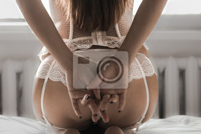 Fototapeta Sexy woman posing from behind in white lace lingerie. Boudoir. The fantasy image of sensual beauty returns to erotica. Beautiful buttocks.