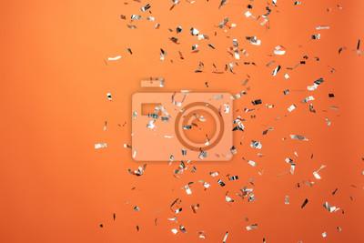 Fototapeta shiny silver confetti on orange background