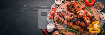 Fototapeta Shish kebab na szaszłyki z cebulą. Na czarnym drewnianym stole.