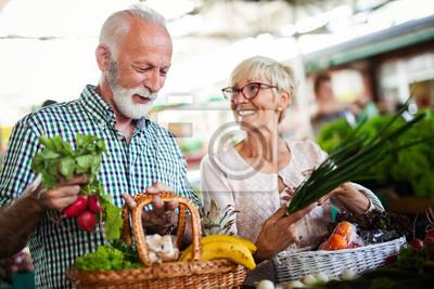 Fototapeta Shopping, food, sale, consumerism and people concept - happy senior couple buying fresh food