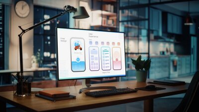 Fototapeta Shot of a Desktop Computer with Food App User Interface Developing Software Standing on the Wooden Desk in the Creative Cozy Living Room. In the Background Warm Evening Lighting and Open Space Studio.