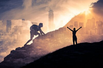 Fototapeta Silhouette of a person climbing to the top of a mountain. Female with arms up to the sky. Strong man, and woman, Winning, success , inspiration and life goals concept.