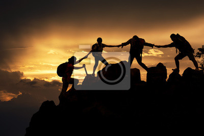 Fototapeta Silhouette of Hikers climbing up mountain cliff. Climbing group helping each other while climbing up in sunset. Concept of help and teamwork, Limits of life and Hiking success full.