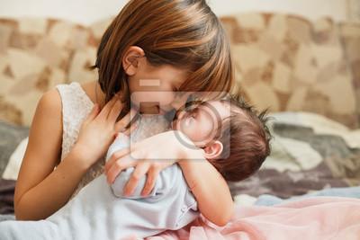 Fototapeta Siostra tulenie swojego nowonarodzonego brata. Maluch spotyka nowego rodzeństwa. Śliczna dziewczyna i nowonarodzony chłopiec relaksujemy w domowej sypialni. Rodzina z dziećmi w domu. Miłość, zaufanie