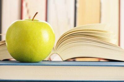 Fototapeta Skład z zielonym jabłkiem i książki na stole