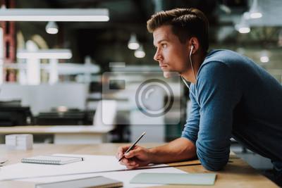 Fototapeta Skoncentrowany inteligentny młody człowiek angażujący się w swoje pomysły podczas rysowania