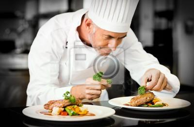 Fototapeta Skoncentrowany mężczyzn kucharz ozdoby potraw w kuchni