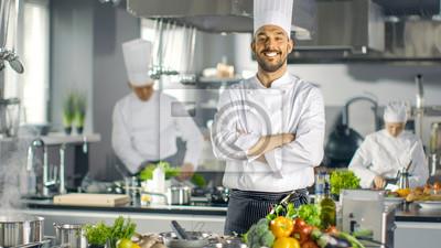 Fototapeta Sławny szef kuchni wielkiej restauracji Krzyż broni i uśmiecha się w nowoczesnej kuchni. Jego pracownicy pracujący w tle.